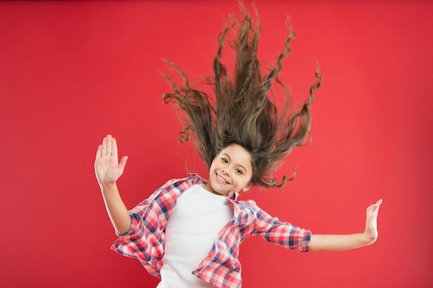 Cabelo comprido incrível. linda garota pequena com cachos de cabelo comprido acenando sobre fundo vermelho. adorável criança cuidando de longos cabelos castanhos. desfrutando de um penteado longo encaracolado.