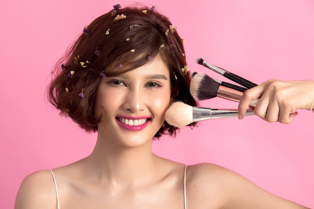Cabelo curto asiático jovem mulher bonita aplicar escova de pó cosmético
