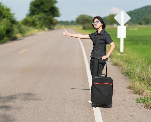 Cabelo curto de mulher com bagagem pedindo carona e polegares para cima