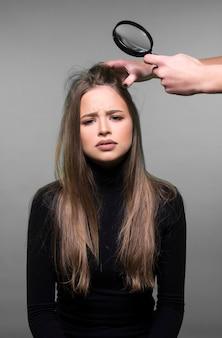 Cabelo danificado, caspa, conceito de cuidados com o cabelo e couro cabeludo. jovem tendo seu cabelo verificado, mão segurando a lupa.