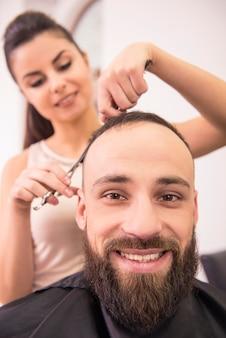 Cabelo de corte cabeleireiro feminino de cliente homem sorridente.