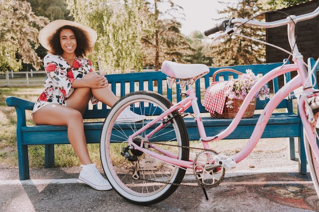 Cabelo encaracolado de sagacidade de garota está sentado no banco do parque ao lado de bicicleta