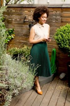 Cabelo encaracolado jovem mulher com um telefone na mão no pátio