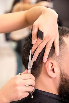 Cabelo fêmea do corte do cabeleireiro do close-up do cliente do homem.