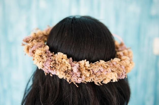 Cabelo feminino com coroa de flores no fundo da natureza.