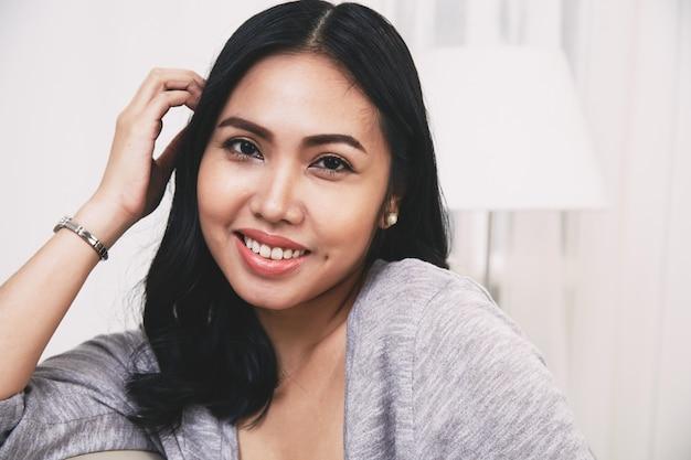 Cabelo filipino alegre da mulher que toca no cabelo