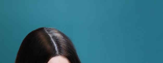 Cabelo grisalho e cabelo tingido em uma cabeça feminina em um fundo azul. formato de banner de conceito de envelhecimento precoce