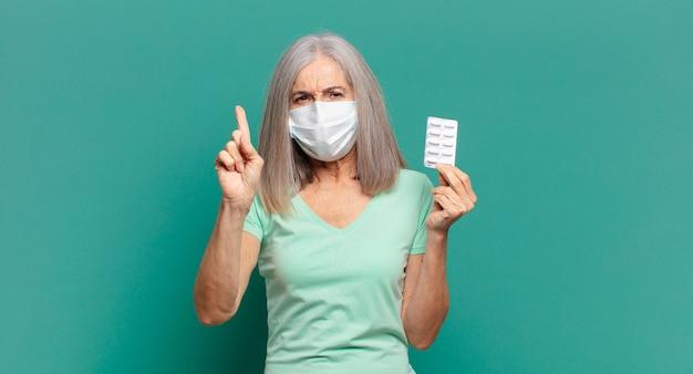 Cabelo grisalho. linda mulher com máscara protetora e comprimidos