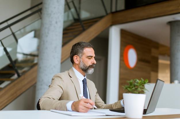 Cabelo grisalho senior empresário trabalhando no laptop no escritório moderno