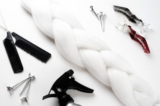 Cabelo kanekalon branco na superfície branca com pentes e acessórios de cabelo