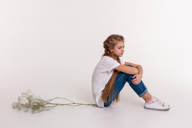 Cabelo longo e claro. jovem chateada com cabelo extremamente comprido sentada em postura fechada no chão