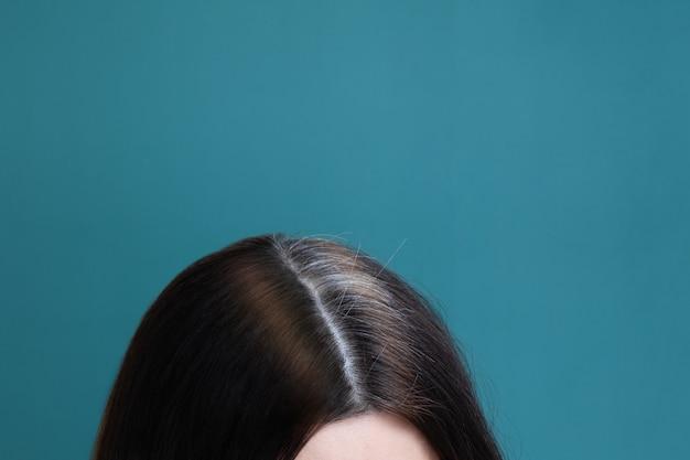 Cabelo meio tingido e cinza em uma cabeça feminina sobre um fundo azul. conceito de envelhecimento precoce