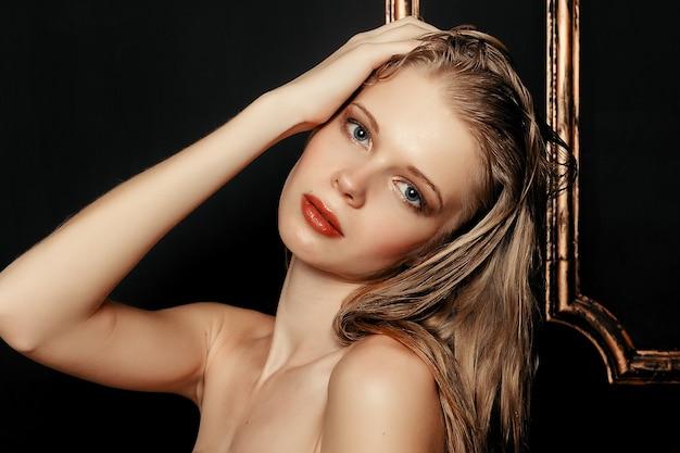 Cabelo molhado beleza moda modelo menina maquiagem natural sobre fundo dourado preto em tons quentes. retrato de jovem com maquiagem fashion