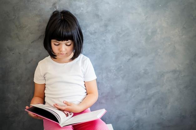 Cabelo preto bonito menina lendo livro pela parede