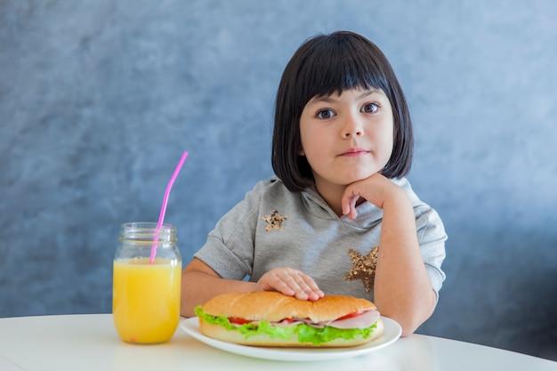 Cabelo preto bonito menina tomando café da manhã e bebendo suco de laranja em casa