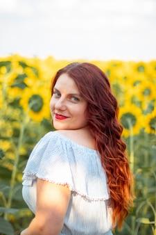 Cabelo ruivo jovem mulher caucasiana no verão algodão vestido em um campo de girassóis amarelos em um dia ensolarado