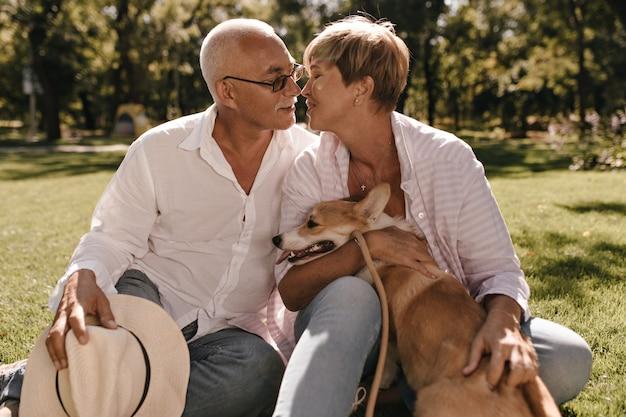 Cabelos curtos em blusa rosa listrada, posando com pequeno corgi e beijando o homem com bigode em camisa branca e jeans no parque.
