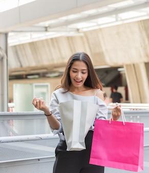 Cabelos longos bonitos menina asiática com sacos de papel coloridos em shopping