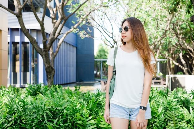 Cabelos longos de menina asiática hipster em branco em branco t-shirt está de pé no meio da rua