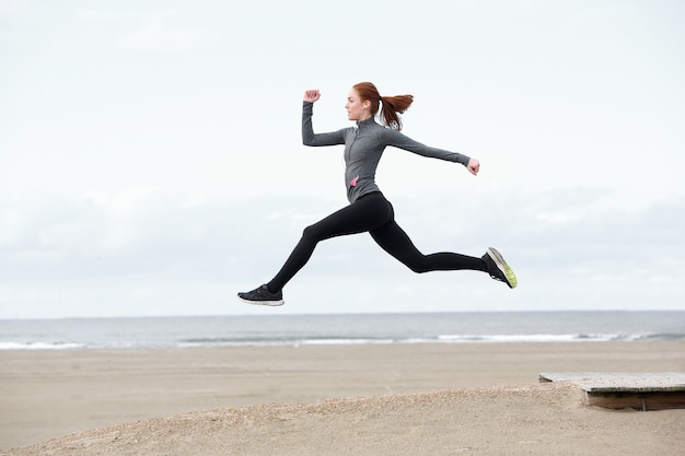 Caber a jovem mulher correndo e pulando