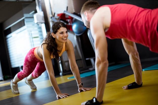 Caber esportiva homem e mulher fazendo exercício de núcleo de prancha