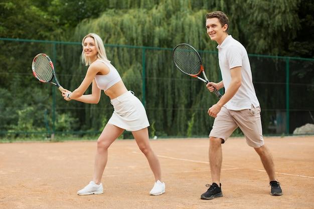 Caber jovem casal jogando tênis