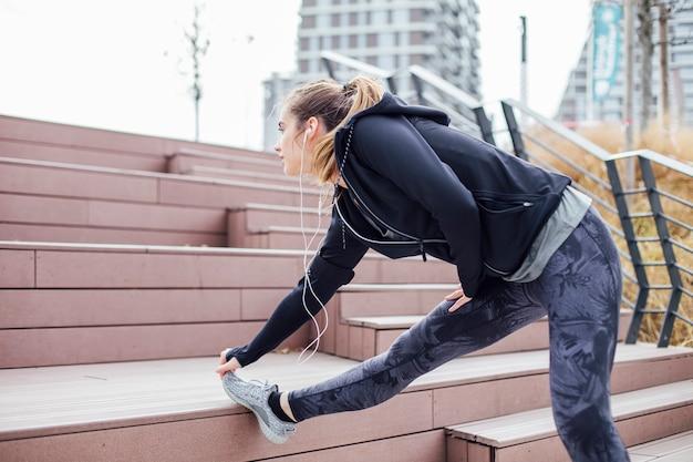 Caber jovem com fones de ouvido fazendo exercícios de alongamento nas escadas ao ar livre
