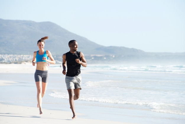 Caber jovem e mulher correndo ao longo da praia