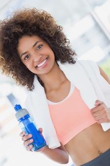 Caber jovem fêmea segurando a garrafa de água no ginásio