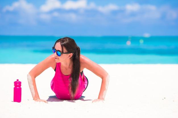 Caber jovem na praia tropical em seu sportswear
