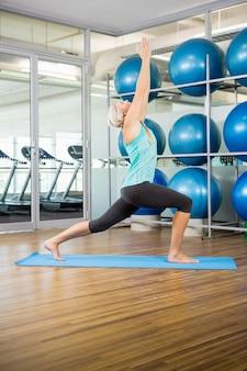 Caber loira fazendo yoga na esteira no estúdio