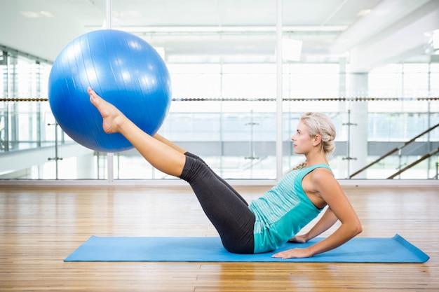 Caber loira na esteira segurando com pernas bola de fitness no estúdio