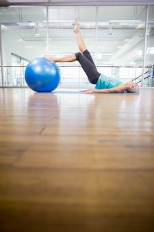 Caber loira no tapete exercitar com bola de fitness no estúdio