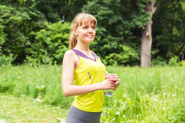 Caber mulher ao ar livre, segurando uma garrafa de água