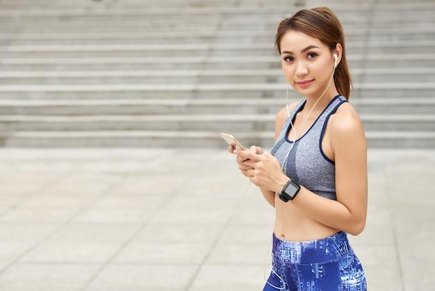 Caber mulher asiática no sportswear, com fones de ouvido e smartphone posando na rua