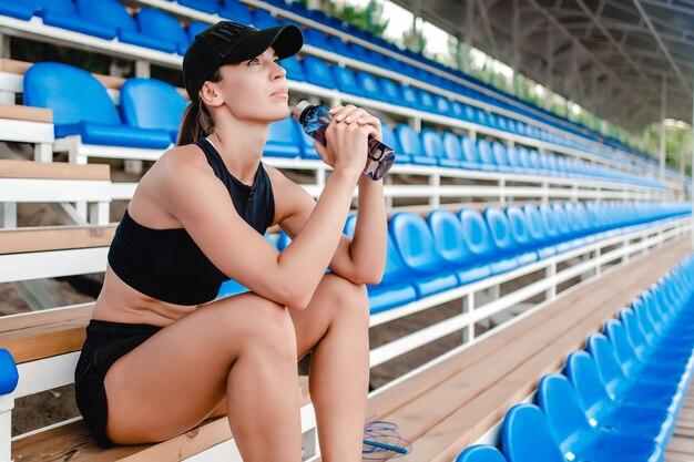 Caber mulher bebendo água durante o treinamento esportivo no estádio