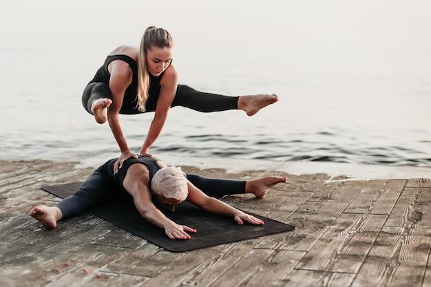 Caber mulher desportiva fazendo parada de mãos em acro yoga asana na praia perto do mar