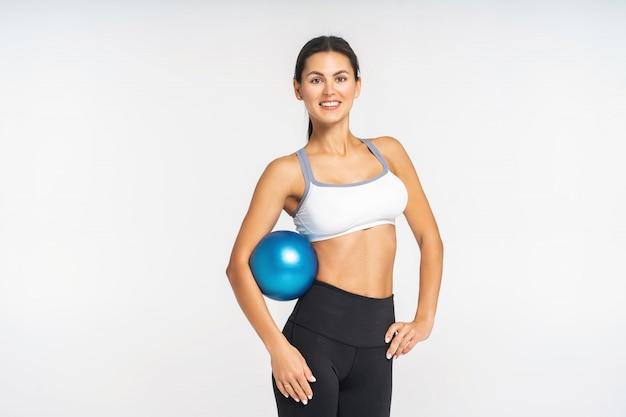 Caber mulher em pé e segurando uma bola de pilates, em uma academia