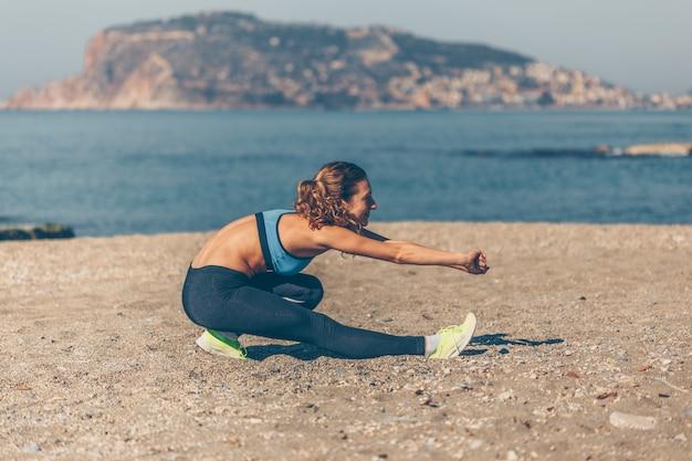 Caber mulher em roupas fitness, fazendo exercícios de aquecimento na praia durante o dia com o mar