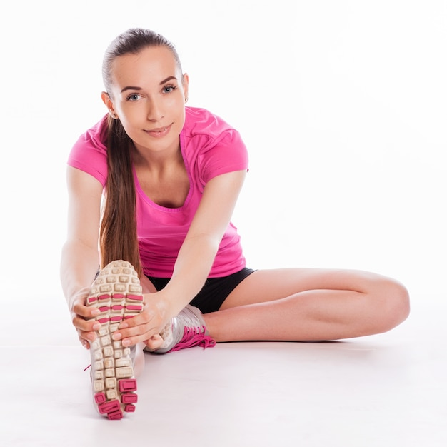 Caber mulher esticando a perna para aquecer - isolado sobre fundo branco