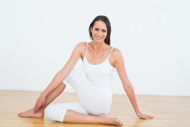 Caber mulher fazendo a meia torção da coluna vertebral no estúdio de fitness