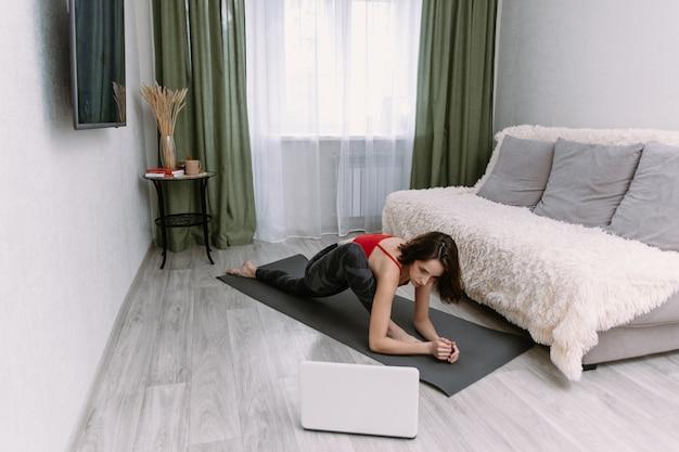 Caber mulher fazendo prancha de ioga e assistindo tutoriais on-line no laptop