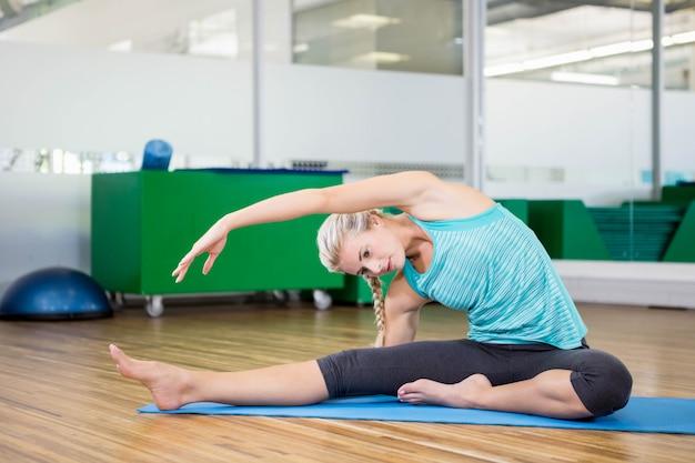 Caber mulher fazendo yoga na esteira no estúdio de fitness