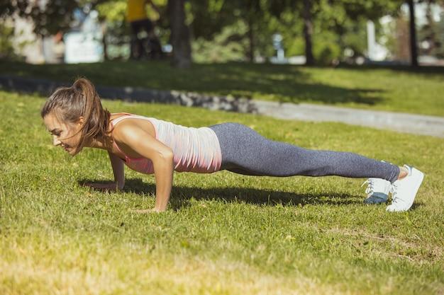 Caber mulher fitness fazendo exercícios de alongamento ao ar livre no parque