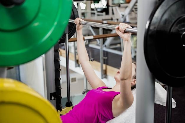 Caber mulher levantando o supino de barra no ginásio