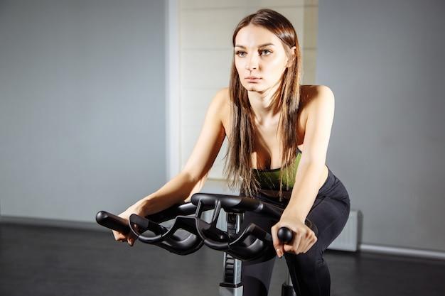 Caber mulher malhando na bicicleta ergométrica no ginásio
