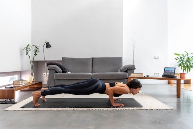 Caber mulher praticando pose de chaturanga usando o programa de treinamento de ioga on-line no tablet em casa