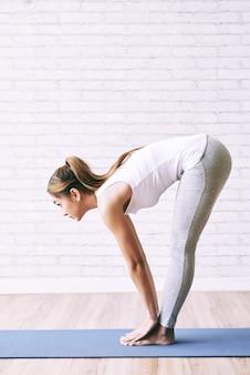 Caber mulher saudável fazendo curva para a frente na aula de yoga