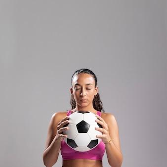 Caber mulher segurando bola de futebol