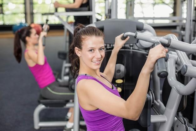 Caber mulher usando máquina de peso no ginásio